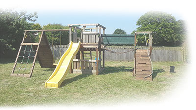 enclosed children's play area with swings, slide and climbing frame